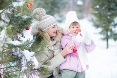 Happy parent and kid playing with christmas tree Stock Images
