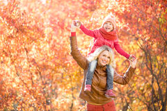 Happy parent and kid walking together outdoor in autumn park. Yellow and red tree leaves. Child sitting on her mothers neck Stock Images