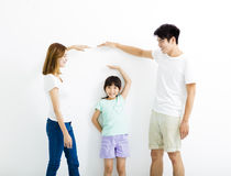 Happy parent measures the growth of   daughter. Happy asian parent measures the growth of   daughter Royalty Free Stock Image