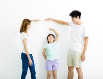 Happy parent measures the growth of   daughter. Happy asian parent measures the growth of   daughter Stock Image