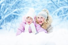 Happy parent mother and kid lying in snow outdoor Royalty Free Stock Photos
