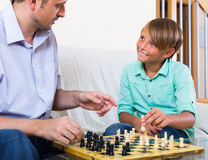 Happy parent and son playing chess Royalty Free Stock Photos