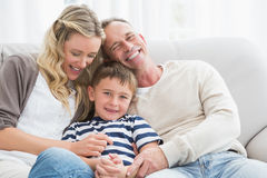 Happy parent tickling her cute son on the couch Stock Images