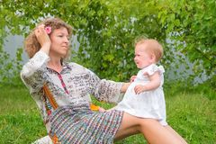 Beautiful little princess. Mother with baby having fun outdoor. stock image