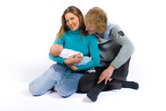 Happy parents. A smiling young couple cradling their newborn baby while sitting on the floor Stock Image