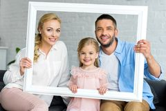 happy parents with adorable little daughter holding white frame and smiling stock photos