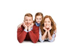 happy parents with adorable little daughter lying together and smiling at camera royalty free stock images