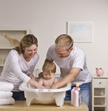 Happy Parents Bathing Baby Stock Photo