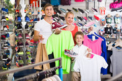 Happy parents with boy in sport store. Happy parents with boy in school age shopping clothing in sport store Royalty Free Stock Image