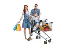 Happy parents carrying cute little son sitting in shopping trolley royalty free stock images
