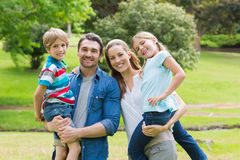 Happy parents carrying kids at park Royalty Free Stock Photo