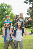 Happy parents carrying kids on shoulders at park Royalty Free Stock Image