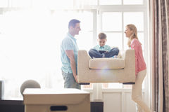 Happy parents carrying son on armchair in new house Stock Image