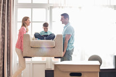 Happy parents carrying son on armchair in new house Stock Photos