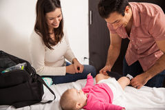 Happy parents changing their baby Stock Images