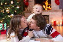 Happy parents and child boy have a fun near Christmas tree at home. Father, mother, son celebrating New Year together. Happy parents and child have a fun near Stock Photo