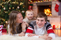 Happy parents and child boy have a fun near Christmas tree at home. Father, mother, son celebrating New Year together Stock Photo