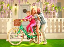 Happy parents with a child, daughter, learn to ride a bike, family lifestyle summer vacations at home royalty free stock images