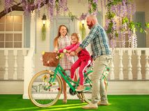 Happy parents with a child, daughter, learn to ride a bike, family lifestyle summer vacations at home stock photography