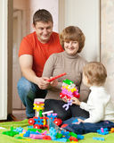 Happy parents and child plays with meccano Royalty Free Stock Photography