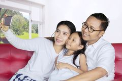 Happy parents with child taking photo at home Stock Images