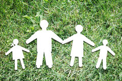 Happy parents with children on backdrop of green grass Royalty Free Stock Image
