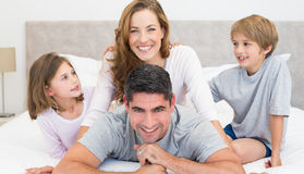 Happy parents and children in bed Royalty Free Stock Photos