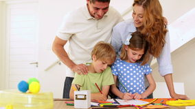 Happy parents and children drawing together at the table looking at camera stock footage