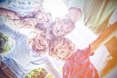 Happy parents with children forming huddle. While standing at yard royalty free stock images