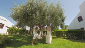Happy parents and children in green garden with big olive tree stock footage