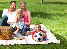 Happy parents and children picnicking in the park Stock Image