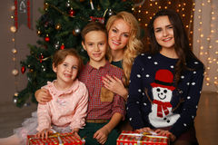 Happy parents and children sharing Christmas hugs Stock Image