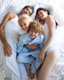 Happy parents and children together on bed Stock Images
