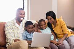 Happy parents and children using laptop while sitting on sofa. At home Royalty Free Stock Images