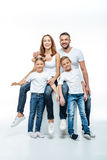 Happy parents with children in white t-shirts. Happy parents with two children in white t-shirts and jeans having fun together and looking at camera royalty free stock images