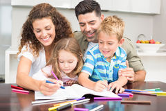 Happy parents colouring with their children at the table Stock Image