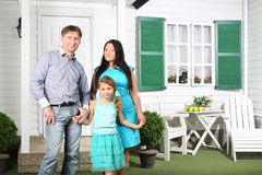 Happy parents and cute little daughter stand next to new house Stock Photo