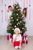Happy parents and daughter with decorated Christmas tree and gif Stock Image