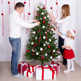 Happy parents and daughter decorating Christmas tree at home Royalty Free Stock Image
