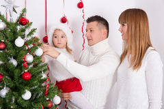 Happy parents and daughter decorating Christmas tree Stock Images