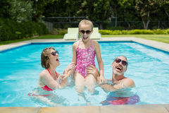 Happy parents and daughter having fun in pool Royalty Free Stock Photos
