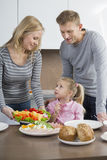 Happy parents with daughter having meal in kitchen Stock Images