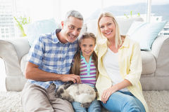 Happy parents and daughter with rabbit in living room Stock Images
