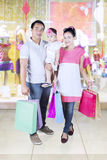 Happy parents and daughter shopping at mall Stock Image