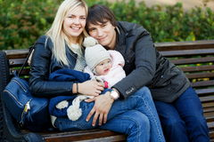 Happy parents with daughter sitting on bench in autumn park Stock Photo