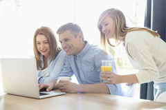 Happy parents with daughter using laptop at home Royalty Free Stock Photos