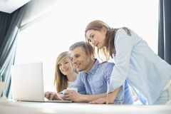 Happy parents with daughter using laptop at home Royalty Free Stock Image