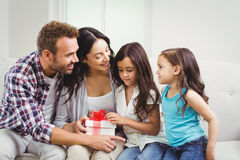 Happy parents with daughters holding gift Stock Images