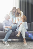 Happy parents with daughters spending quality time in living room Stock Photo