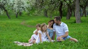 Happy parents with daughters talk and laugh on plaid in spring season park. Happy parents with two daughters talk and laugh sitting on plaid in the beautiful stock video footage